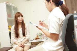 医師の問診を受けている女性
